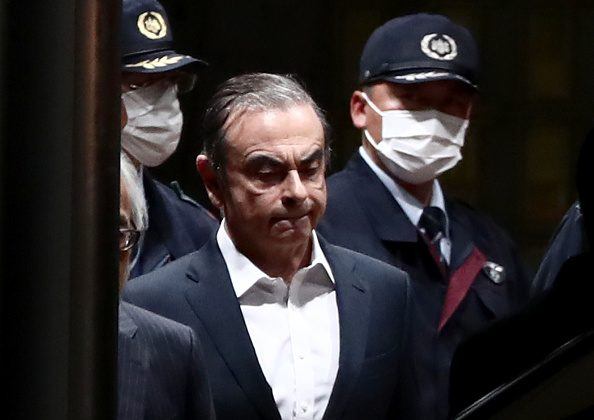 Former Nissan Chairman Carlos Ghosn (C) is escorted as he walks out of the Tokyo Detention House following his release on bail in Tokyo on April 25, 2019. BEHROUZ MEHRI/AFP/Getty Images