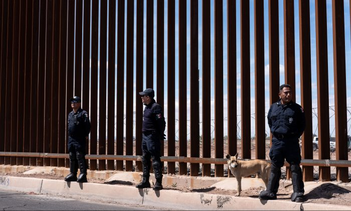 Mexico's federal police stand guard at the US-Mexico border fence as  President Donald Trump visits Calexico, California, as seen from Mexicali, Baja California state, Mexico, on April 5, 2019. (GUILLERMO ARIAS/AFP/Getty Images)