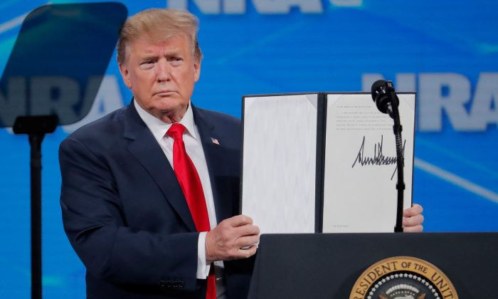 President Trump holds up an executive order he signed at an NRA event Friday April 26, announcing that the United States will drop out of the Arms Trade Treaty that was signed during the Obama administration. (Lucas Jackson/Reuters)