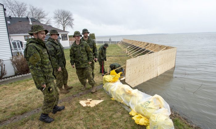 Canadian Forces personnel reinforce a barrier against rising flood waters on April 26, 2019, in Point Calumet, Que. (The Canadian Press/Ryan Remiorz)