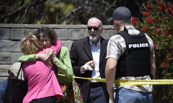 Two people hug as another talks to a San Diego County Sheriff's deputy outside of the Chabad of Poway Synagogue in Poway, Calif., on April 27, 2019.  (Denis Poroy/AP Photo)