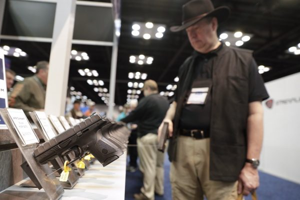 A gun enthusiast looks over the display of Beretta pistols on display in the exhibition hall
