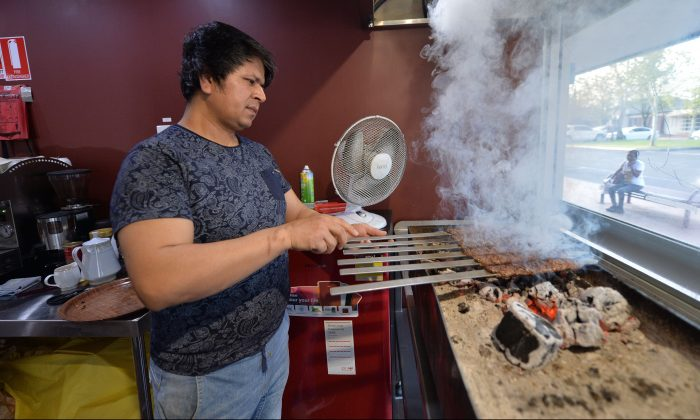 """Hazara refugee Ali cooks kebabs in his """"Afghan Friendship Restaurant"""" on Sept. 28, 2018, in Griffith, a tribute to the warm welcome he says he received after moving to the town five years ago. The 44-year-old father of three is among a growing number of refugees and migrants to Australia who have opted to live in the bush rather than among the bright lights, hustle-bustle and astronomical prices of Sydney or Melbourne. (PETER PARKS/AFP/Getty Images)"""