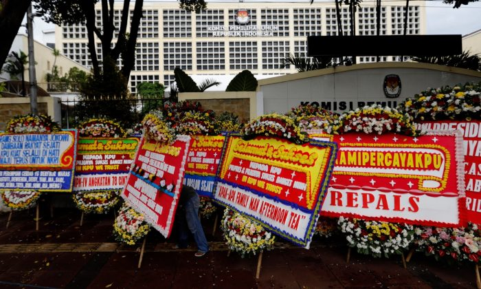 A worker arranges flower wreaths and congratulatory boards from people after this week's election outside General Election Commission (KPU) headquarters in Jakarta, Indonesia on April 21, 2019. (Willy Kurniawan/Reuters)