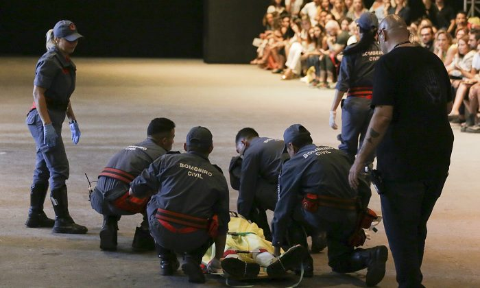 Model Tales Soares is taken from the catwalk by paramedics after he collapsed during Sao Paulo Fashion Week in Sao Paulo, Brazil, on April 27, 2019. (Leco Viana/Thenews2 via AP)