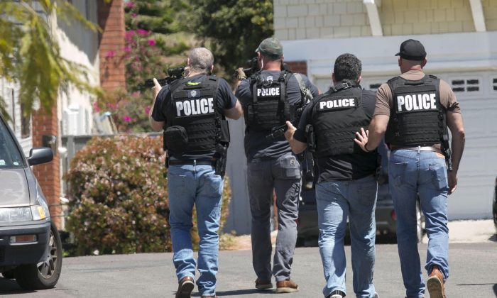 Heavily armed San Diego police officers approach a house thought to be the home of 19 year-old John T. Earnest, who is a suspect in the shooting of several people in a Poway synagogue in San Diego, Calif., on April 27, 2019. (John Gibbins/The San Diego Union-Tribune via AP)