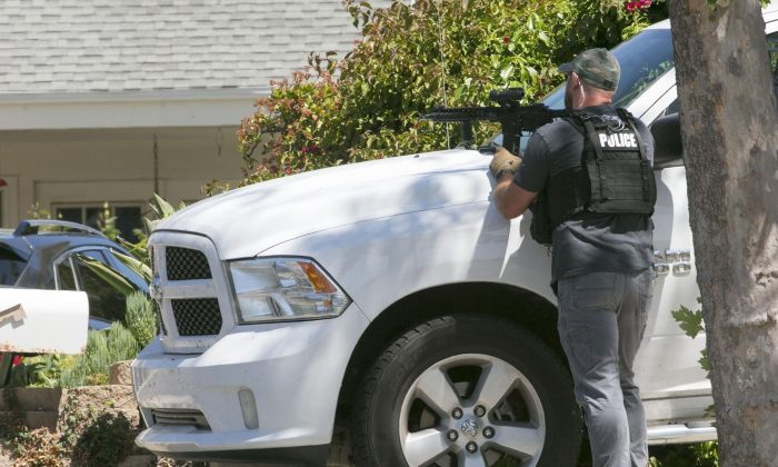 A San Diego Police officer keeps aim on the house thought to be the home of 19 year-old John T. Earnest, who is a suspect in the shooting of several people in a Poway synagogue in San Diego, Calif., on April 27, 2019. (John Gibbins/The San Diego Union-Tribune via AP)