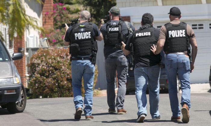 Heavily armed San Diego police officers approach a house in this file photo taken in San Diego, Calif., on April 27, 2019. (John Gibbins/The San Diego Union-Tribune via AP)