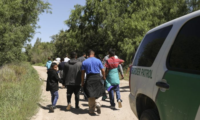A group of illegal aliens walk up the road after crossing the Rio Grande from Mexico. Further up the road, they will be processed by Border Patrol and then board a bus bound for the Border Patrol processing facility in McAllen, Texas, on April 18, 2019. (Charlotte Cuthbertson/The Epoch Times)