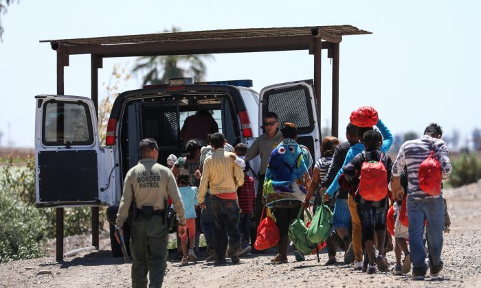 A group of illegal aliens is processed by Border Patrol agents after crossing from Mexico into Yuma, Ariz., on April 13, 2019. (Charlotte Cuthbertson/The Epoch Times)