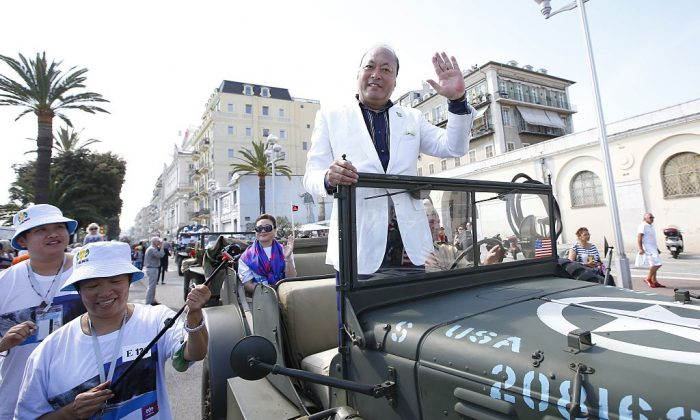 Chinese businessman and CEO Tiens Group, Li Jinyuan (C), parades in Nice as part of a celebration for the 20th anniversary of his company, on May 8, 2015. His company was revealed to be running a pyramid scheme. (VALERY HACHE/AFP/Getty Images)