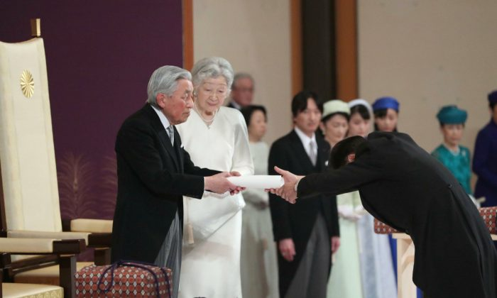 Japan's head of state Akihito hands over his statement to the grand chamberlain during the ceremony of his abdication at the Imperial Palace in Tokyo, Tuesday, April 30, 2019. The 85-year-old Akihito ends his three-decade reign on Tuesday. (Japan Pool via The Associated Press)