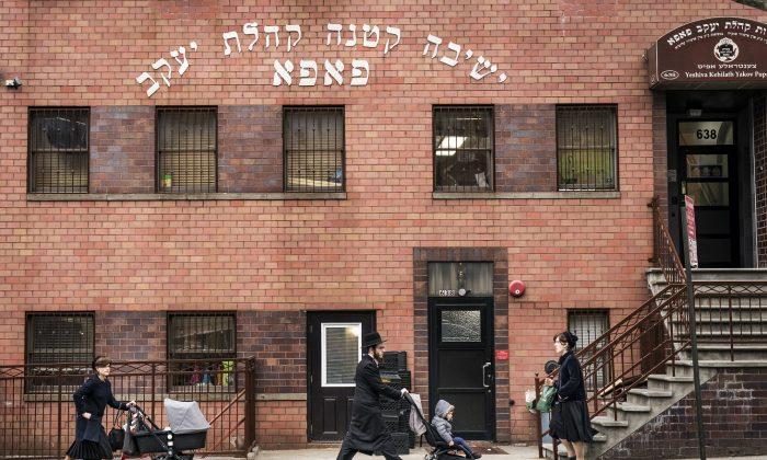 Pedestrians walk past the Yeshiva Kehilath Yakov School in the Williamsburg neighborhood of Brooklyn, N.Y., on April 9, 2019.  (Drew Angerer/Getty Image)