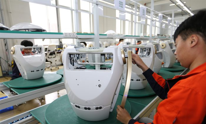 Workers assemble robots at the production line of Chuangze Intelligent Robot in Rizhao, Shandong Province, China on April 29, 2019.  (Reuters)