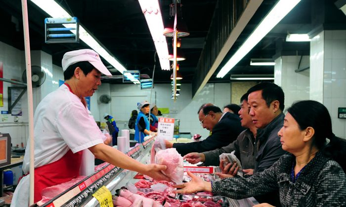 Chinese customers buy pork at a supermarket in Jiujiang, east China's Jiangxi province.(STR/AFP/Getty Images)