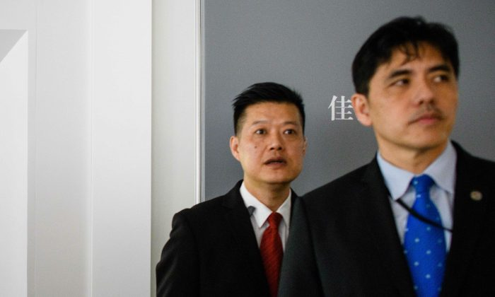This picture taken on October 13, 2017, shows a man (R, wearing blue tie) identified by local Hong Kong media as former CIA agent Jerry Chun Shing Lee standing in front of a member of security at the unveiling of Leonardo da Vinci's 'Salvator Mundi' painting at the Christie's showroom in Hong Kong. (Anthony Wallace/AFP/Getty Images)