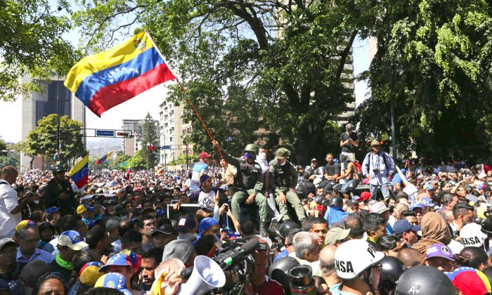 A member of the national guard who reportedly joined Juan Guaidó, recognized internationally as Venezuela's legitimate leader, waves a national flag during a gathering at Altamira Plaza in Caracas on April 30, 2019. (CRISTIAN HERNANDEZ/AFP/Getty Images)