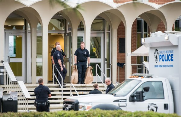Charlotte-Mecklenburg law enforcement stand in front of the Kennedy building where a gunman killed two people and injured four students at UNC Charlotte in Charlotte