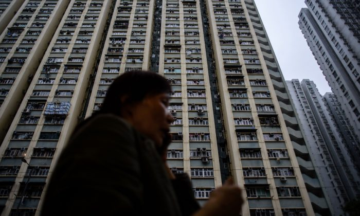 A woman on the phone in front of a high-rise residential building. (Anthony Wallace/AFP/Getty Images)