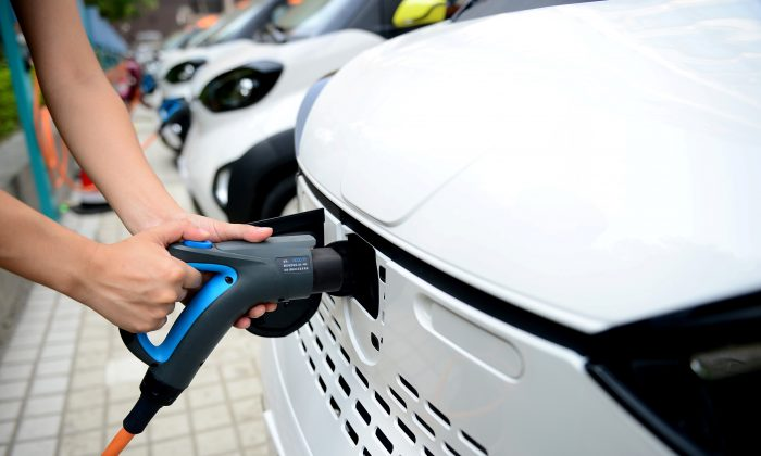 A staff member hooks up a charging cable to an electric vehicle (EV) at a charging station in Liuzhou, Guangxi Zhuang Autonomous Region, China on July 31, 2017. (Reuters)