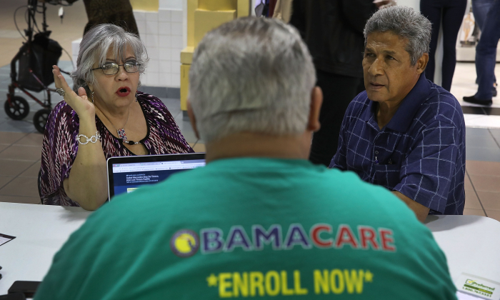 Isabel Diaz Tinoco (L) and Jose Luis Tinoco speak with Otto Hernandez, an insurance agent from Sunshine Life and Health Advisors, as they shop for insurance under the Affordable Care Act at a store setup in the Mall of Americas  on Nov. 1, 2017, in Miami, Fla. (Joe Raedle/Getty Images)