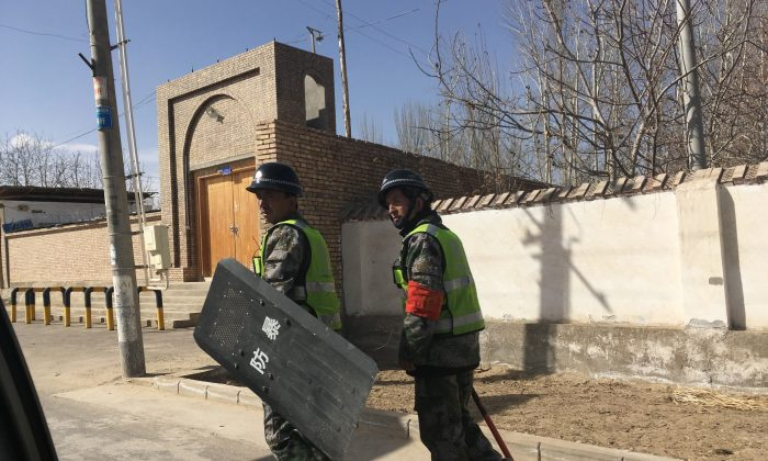 Local police patrol at a village in Hotan prefecture in China's western Xinjiang region on February 17, 2018. (Ben Dooley/AFP/Getty Images)