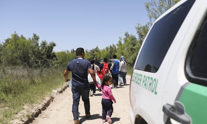 A group of illegal aliens walk up the road after crossing the Rio Grande from Mexico. Further up the road, they will board a bus bound for the Border Patrol processing facility in McAllen, Texas, on April 18, 2019. (Charlotte Cuthbertson/The Epoch Times)