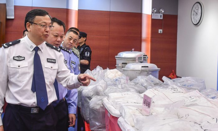 Police officers look at bags of cocaine seized in Guangzhou, Guangdong Province, China on April 24, 2018. (AFP/Getty Images)
