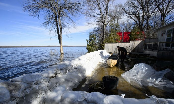 A resident of Fitzroy Harbour, Ont., work to hold back flood waters on the Ottawa River on April 29, 2019. (Sean Kilpatrick/The Canadian Press)