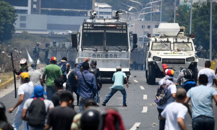 Demonstrators clash with soldiers loyal to Venezuelan dictator Nicolás Maduro after troops joined leader Juan Guaidó in his campaign to oust Maduro's government, in the surroundings of La Carlota military base in Caracas on April 30, 2019. (Federico Parra/AFP/Getty Images)