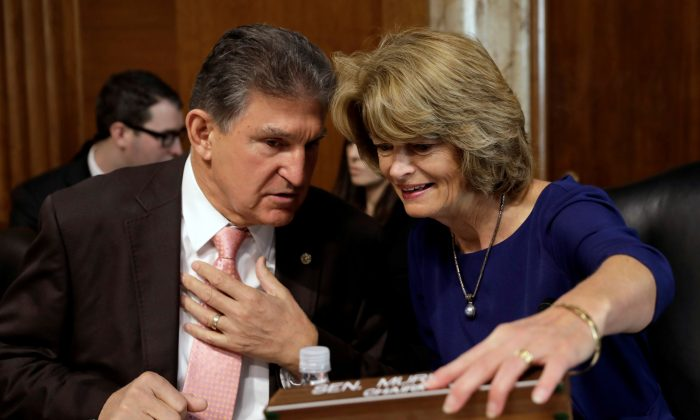 Sens. Joe Manchin (D-W. Va.) and Lisa Murkowski (R-Alaska) chat before a Senate Energy and Natural Resources Committee nomination hearing for former energy lobbyist David Bernhardt to be Interior secretary on Capitol Hill in Washington, on March 28, 2019. (Yuri Gripas/Reuters)