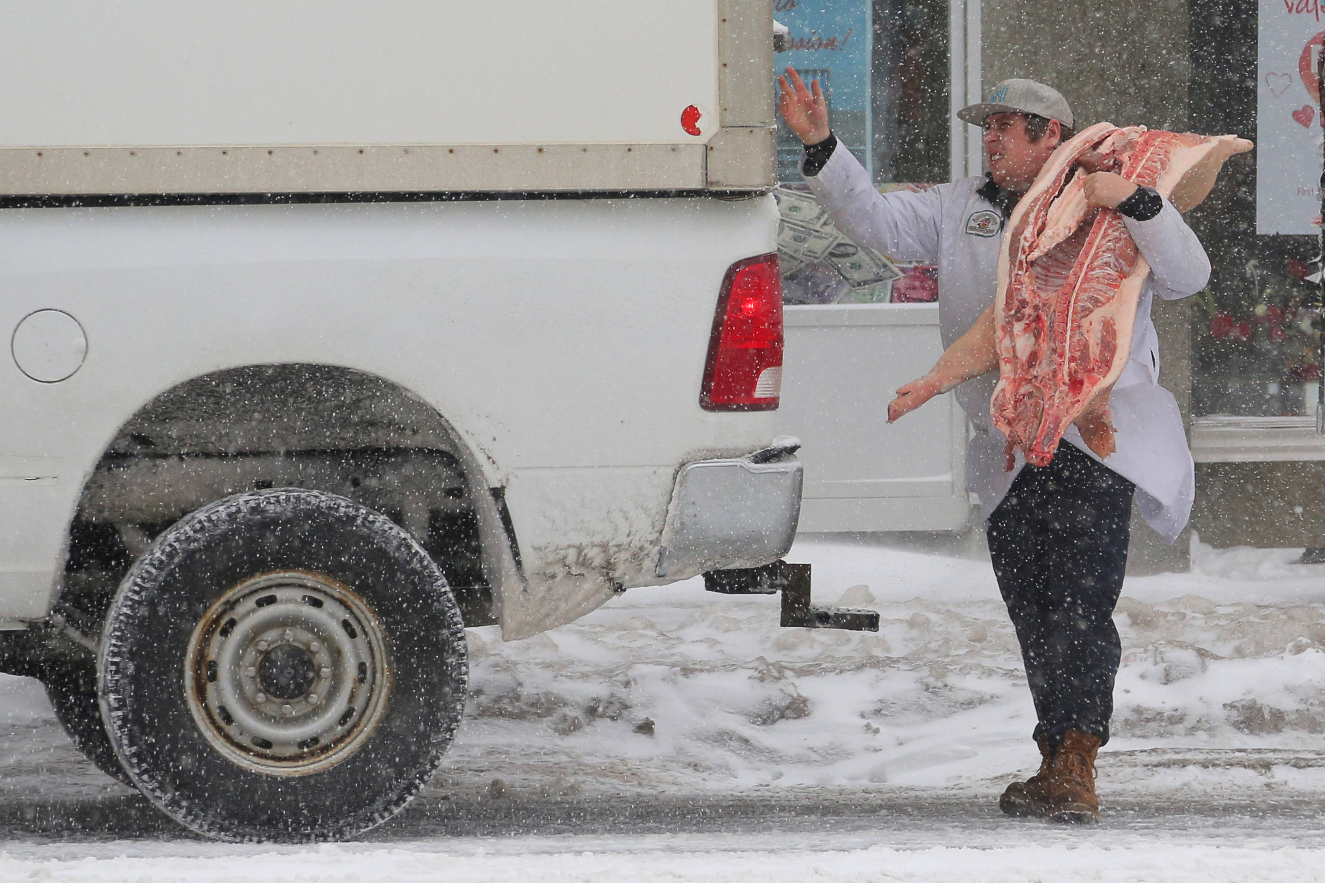 FILE PHOTO: A butcher delivers pork during a snow storm in Toronto