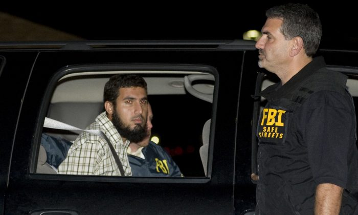 Terrorism suspect Najibullah Zazi is seated in an FBI vehicle after being arrested by the FBI in Aurora, Colo. on Sept. 19, 2009. (Chris Schneider/The Denver Post via AP, File)
