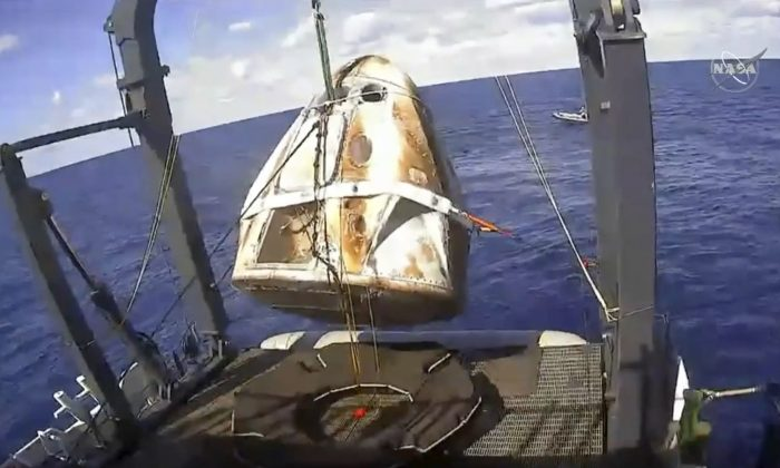 The SpaceX Crew Dragon capsule is hoisted onto a ship in the Atlantic Ocean off the Florida coast after it returned from a mission to the International Space Station on March 8, 2019. (NASA via AP, File)