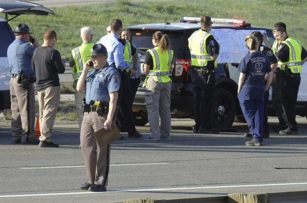 Emergency personnel work at the scene of a deadly collision on Interstate 70