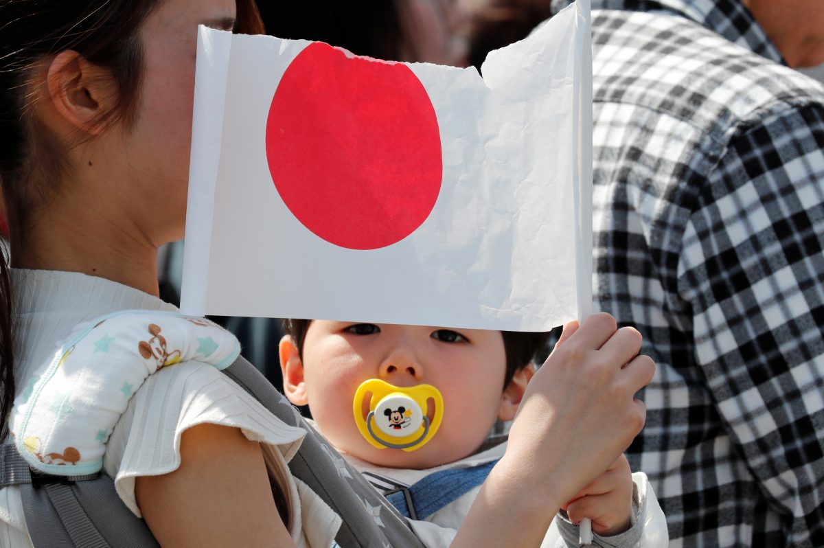 A baby holds a Japanese national flag