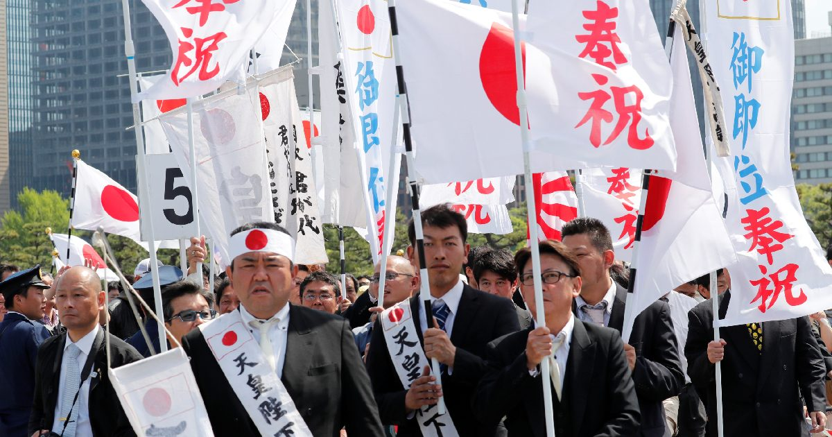 Well-wishers with flags wait in line to enter the Imperial Palace