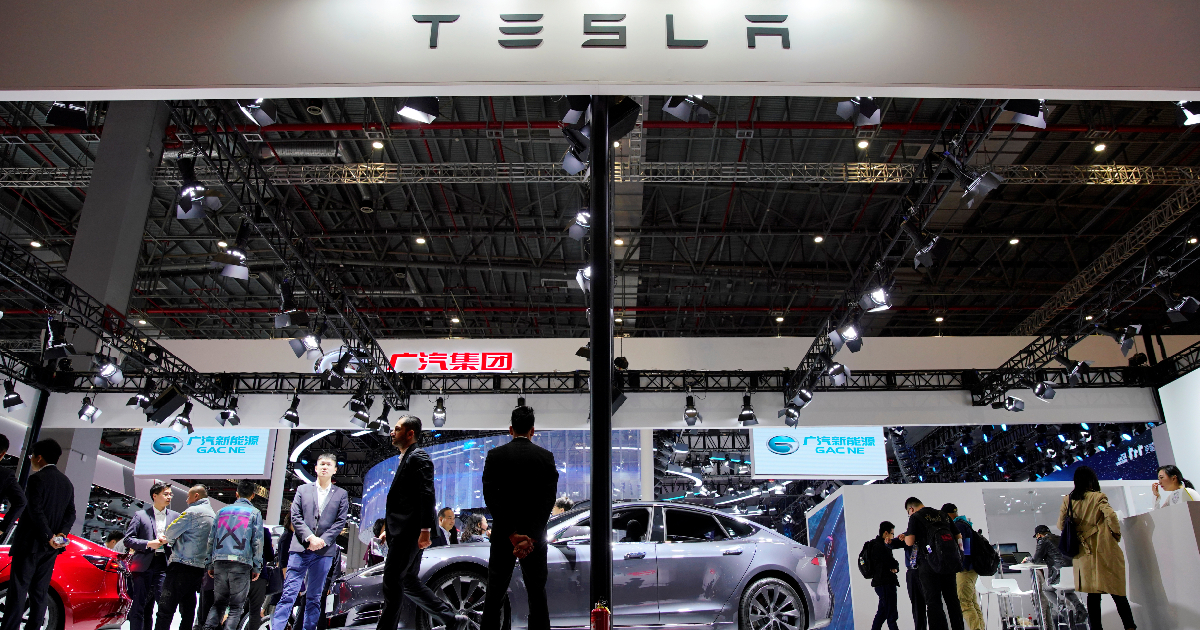People visit a Tesla booth during the media day