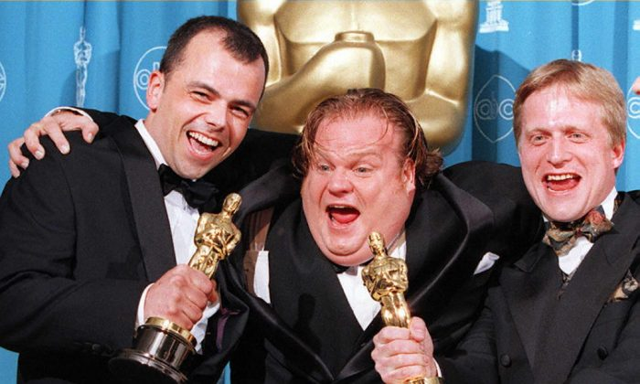 """Comedian-actor Chris Farley (C) poses with filmmakers Tyron Montgomery (L) and Thomas Stellmach (R) after they won an Oscar for best animated short film for """"Quest"""" during the 69th Annual Academy Awards in Los Angeles, Cali., on March 24, 1997. (Vince Bucci/AFP/Getty Images)"""