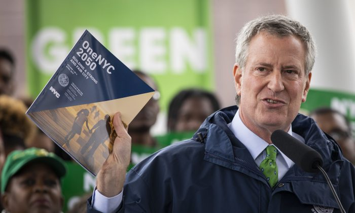 New York City Mayor Bill de Blasio holds up a copy of 'One NYC 2050' as he speaks at Hunters Point South Park in the Queens borough of New York City on April 22, 2019. (Drew Angerer/Getty Images)