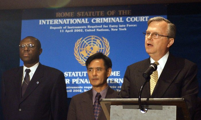United Nations Under Secretary General Hans Corell (R) speaks at ceremony marking the ratification of the Rome statue of the International Criminal Court (ICC) as Democratic Republic of Congo Ambassador to the UN Atoki Ileka (L) and Cambodia Ambassador to the UN Sithong Neav (C) listen after presenting their country's instrument of ratification, 11 April 2002, at UN headquarters in New York. STAN HONDA/AFP/Getty Images