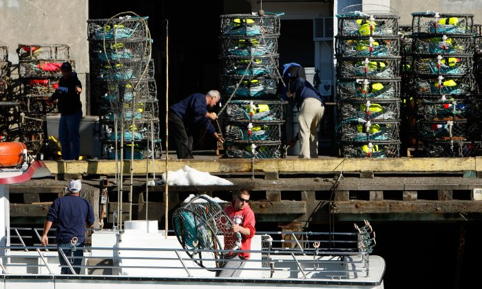 "Crew members aboard the fishing boat ""Outer Limits"" load crab pots onto their boat at Pier 45 in San Francisco, Calif., on Nov. 30, 2007. (Justin Sullivan/Getty Images)"