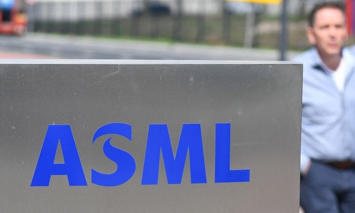 An employee walks past an ASML logo, a Dutch company which is currently the largest supplier in the world of semiconductor manufacturing machines, at the company's headquarters in Veldhoven on April 17, 2018. (EMMANUEL DUNAND/AFP/Getty Images)