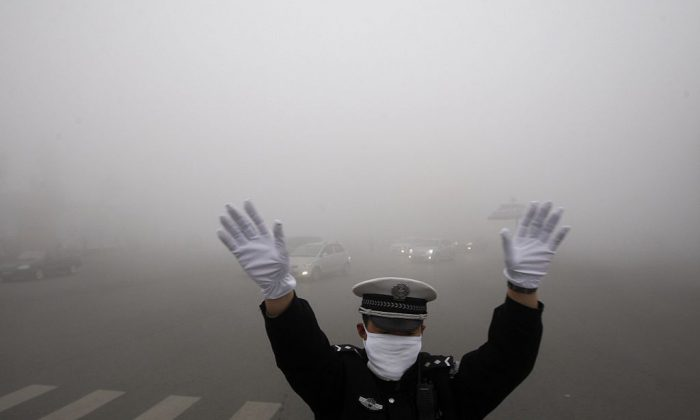 A policeman gestures as he works on a street in heavy smog in Harbin, northeast China's Heilongjiang Province, on Oct. 21, 2013. (STR/AFP/Getty Images)