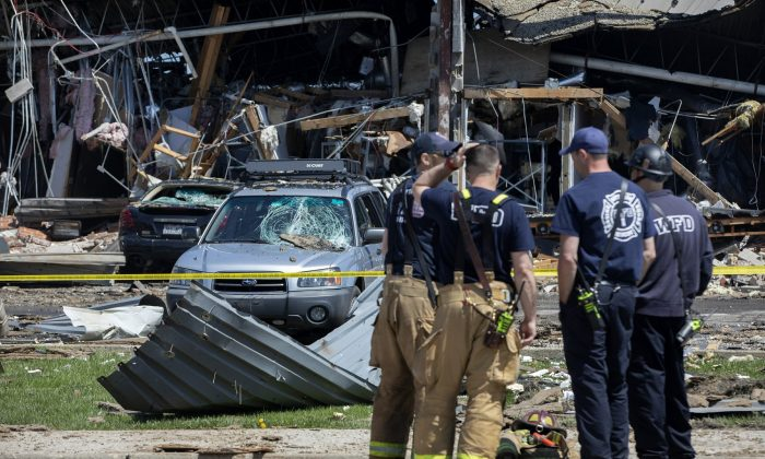 Debris can be seen as emergency personnel and others search and clear the scene of an explosion and fire at AB Specialty Silicones chemical plant in Waukegan, Ill., on May 4, 2019. (Erin Hooley/Chicago Tribune via AP)