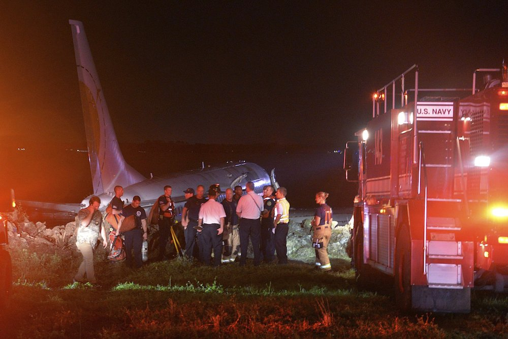 Emergency crews working next to a Boeing 737 aircraft arriving from Naval Station Guantanamo Bay, Cuba, which slid off the runway at Naval Air Station Jacksonville, Fla., into the St. Johns River. (Thomas A. Higgins/U.S. Navy via AP)