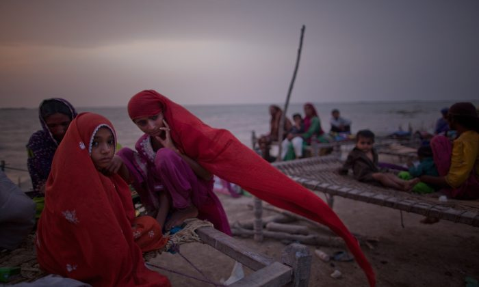 Young girls, whose families were displaced by floods, sit on a makeshift bed, as they take shelter on higher ground in Thatta, Pakistan on Aug. 29, 2010. (Daniel Berehulak/Getty Images)