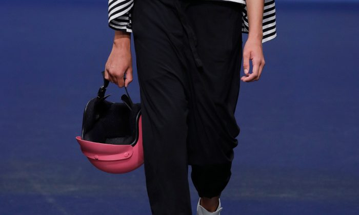 A woman holding a pink helmet. (Andreas Rentz/Getty Images for Platform Fashion)