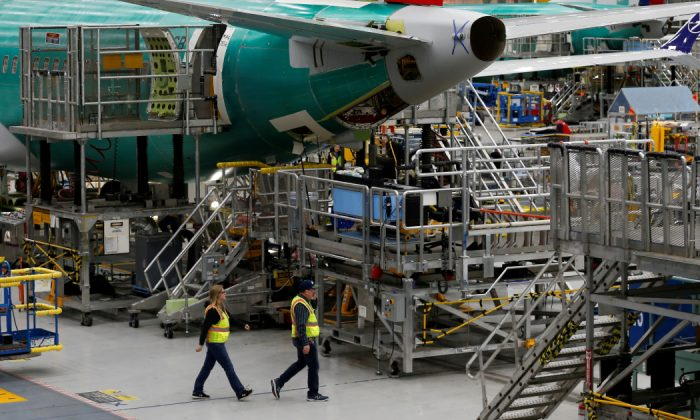 Employees walk by the end of a 737 Max aircraft at the Boeing factory in Renton, Washington, U.S., March 27, 2019. (Lindsey Wasson/Reuters)