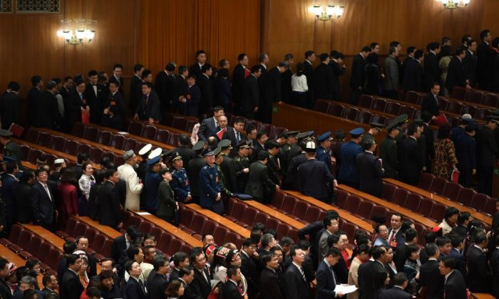 Delegates line up to leave after the closing session of the National People's Congress (NPC) in Beijing's Great Hall of the People when the rubber-stamp parliament approved a foreign investment law on March 15, 2019. (Greg Baker/AFP/Getty Images)
